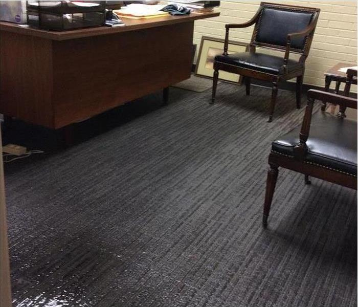 desk, two chair and a wet carpet of an office. Concept of water damage in an office