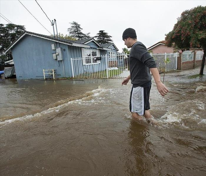 person walking through flooded street
